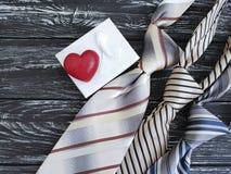 La cravatta, cuore, simbolo festivo della carta del contenitore di regalo romantico celebra il vecchio fondo di legno nero, il gi Fotografia Stock