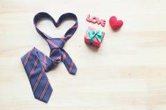 La cravatta del cuore ed il contenitore di regalo con il nastro e fatto a mano lavorano all'uncinetto sentono fotografie stock libere da diritti