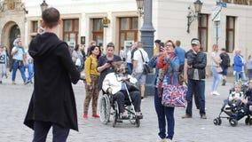 La creatividad de la calle, músico está jugando en el violín en la plaza para los espectadores almacen de metraje de vídeo
