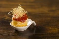 La crema batida del queso de la canasta con la jalea de la guayaba y la harina de maíz cremosa se apelmazan en una cuchara fotografía de archivo