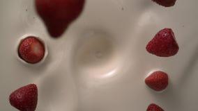 La crema blanca del yogur con las fresas del torbellino cae abajo con salpica en tiro del tablero de la mesa de la cámara lenta almacen de metraje de vídeo