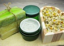 La crema cosmetica per cura e la margherita del fronte fiorisce il sapone natual Immagine Stock