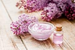 La crema organica, l'estratto in cosmetico lilla ha messo con i fiori sul fondo di legno della tavola Immagini Stock