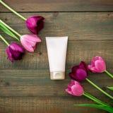 La crema para la piel y los tulipanes florece en fondo de madera Composición de la belleza Endecha plana, visión superior Fotos de archivo
