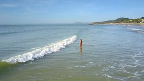 La cresta de onda espumosa lava a la muchacha en el mar debajo del cielo azul