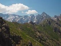 la cresta della montagna rocciosa con neve ha macchiato il backround delle montagne fotografia stock