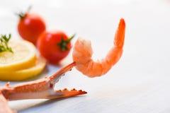 La crevette sur le citron de tomate de griffes de crabe décorent sur le fond de table de salle à manger photographie stock