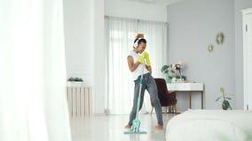 La criada alegre de la muchacha bonita de la raza mixta está limpiando el piso en plano hermoso con la fregona plástica y está es almacen de metraje de vídeo