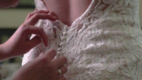 La criada del honor ayuda a los botones cercanos de la novia en el vestido de boda del cordón metrajes