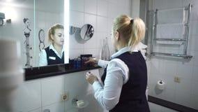 La criada en uniforme pone el gel de la ducha para los visitantes Interior hermoso del cuarto de baño en hotel moderno metrajes