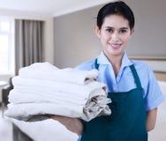 La criada está sosteniendo las toallas Imágenes de archivo libres de regalías
