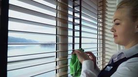 La criada frota las persianas en la habitación El ama de casa limpia el sitio en hotel moderno almacen de video