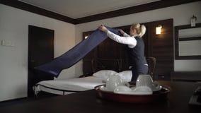 La criada hace una cama matrimonial en una habitación pequeña, acogedora metrajes