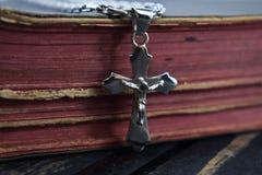 La croix argentée se trouve sur la vieille Sainte Bible Image libre de droits