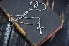 La croix argentée se trouve sur la vieille Sainte Bible Images libres de droits