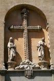 La croix catholique et deux figures dans la voûte sur le mur du bâtiment Image stock