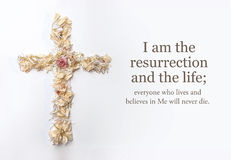 La croix de Pâques faite de fleurs et la bible de John passent Photographie stock libre de droits
