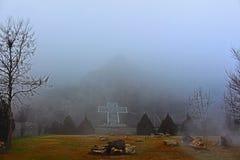 La croix de Rupite et le bâti Kojuh par l'hiver et le temps brumeux Photo stock