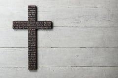La croix en bois foncée avec a découpé la prière du ` s de seigneur sur le fond en bois blanc usé Images stock