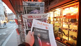 La Croix newspapers about Donald Trump new USA president. PARIS, FRANCE - NOV 10, 2016: Man buying LA Croix newspaper with shocking headline title at press kiosk stock video footage