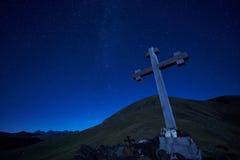 La croix se connectent le passage de crête de montagne la nuit Images stock