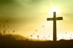 La croix sur le coucher du soleil Images stock