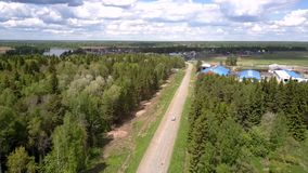 La cruce conduce al pueblo a lo largo del camino gris cerca de bosques almacen de video