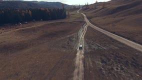 La cruce negra grande monta a lo largo de un camino polvoriento de la montaña del desierto, alrededor metrajes