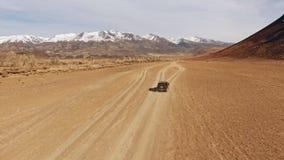 La cruce negra monta a lo largo de un camino polvoriento de la terracota de la montaña del desierto metrajes