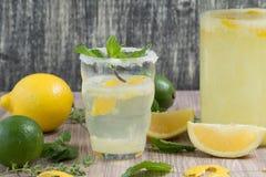 La cruche et le verre de whith de limonade monnayent sur la table en bois image libre de droits