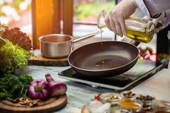 La cruche verse le liquide sur la casserole image stock