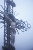 La crucifixion de la statue de Jesus Christ en neige et brouillard Photos libres de droits