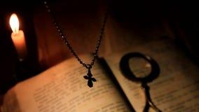 La cruz cuelga sobre un libro de oración con una vela ardiente metrajes