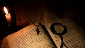 La cruz cuelga sobre un libro de oración con una vela ardiente almacen de metraje de vídeo