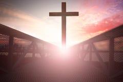 La cruz de Jesus Christ en el paso elevado en la puesta del sol Imagenes de archivo
