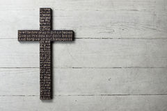 La cruz de madera oscura con talló el rezo del ` s del señor en fondo de madera blanco gastado imagenes de archivo