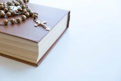 La cruz de madera y la biblia negra en fondo de madera foto de archivo