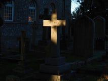 La cruz de piedra en un cementerio se encendió por el sol de la mañana con las palabras Jesu Mercy Fotografía de archivo
