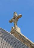 La cruz de piedra envejecida de una iglesia en un cielo azul brillante Foto de archivo libre de regalías