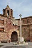 La cruz del límite y la puerta antigua en la ciudad española Prades Imagen de archivo