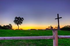 La cruz está sobre la cerca y a través de la hierba Imagenes de archivo