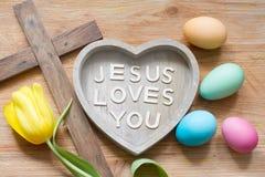 La cruz y el corazón de Pascua con la inscripción Jesús le ama en tablero de madera abstracto de la primavera fotos de archivo libres de regalías