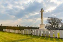 La cruz y las lápidas mortuarias en el CEMENTERIO CONMEMORATIVO de DUNKERQUE, Dunkerque, Francia con Sun irradia en el cielo nubl Imagen de archivo libre de regalías