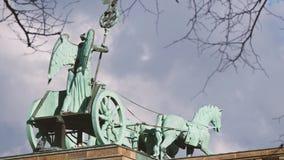 La cuadriga de la puerta de Brandeburgo detrás de ramas en Berlín, Alemania, enfoca hacia fuera metrajes