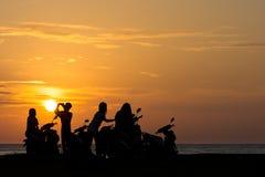 La cuadrilla del grupo de adultos jovenes de los adolescentes mira un lado de la playa asolear el sistema Foto de archivo