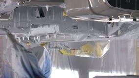 La cubierta anticorrosiva de automóviles basa, los robots está irrigando el metal almacen de video