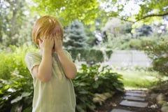 La cubierta de la muchacha observa en jardín Imagen de archivo