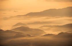 La cubierta de la niebla las altas montañas en Tailandia septentrional cuando la salida del sol Fotos de archivo libres de regalías
