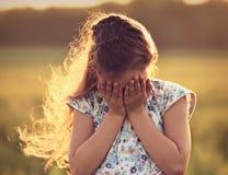 La cubierta infeliz gritadora de la muchacha del niño hace frente a las manos en la naturaleza del verano Imagen de archivo
