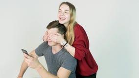 La cubierta sonriente feliz hermosa de la mujer observa con sus manos del hombre joven hermoso en humor de la diversión almacen de metraje de vídeo